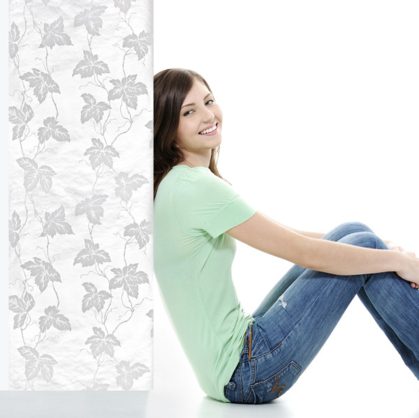 Young happy female sitting on the floor near white blank banner